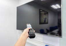 Smart TV remote control in woman hand Royalty Free Stock Image