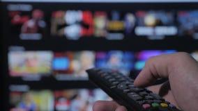 Smart TV Video servizio scorrente online con i apps e la mano La tenuta maschio della mano a distanza il controllo gira fuori dal stock footage