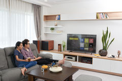 Smart tv. Vietnamese young couple watching smart tv at home Stock Photography