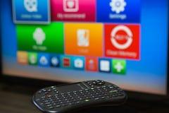 Smart tvkontrollapparat på bakgrunden av TVskärmen royaltyfria foton