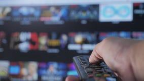 Smart tvlivsstil Online-video strömmande service med apps och handen Manliga det avlägsna handinnehavet kontrollen vänder av arkivfilmer