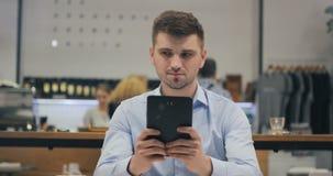 Smart ung arbetare för kontor för chef för affärsmanadvokatdoktor som använder hans minnestavla på lunchtimen i kafé arkivfilmer