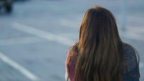 Smart ung brunhårig flicka som tillbaka staing till kameran och väntar på någon Steadicam långsamt mo skott lager videofilmer