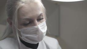 Smart ung cosmetologyspecialist med den långa ganska hästsvansen lager videofilmer