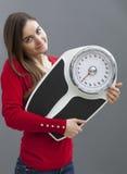 Smart ung kvinna som rymmer hennes skala med tillfredsställelse för viktkontroll Arkivfoton