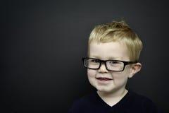 Smart ung pojke som ha på sig exponeringsglasinfront av en blackboard Arkivbilder