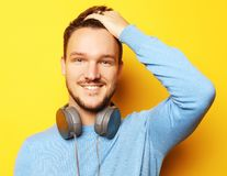 Smart ungt le mananseende mot gul bakgrund arkivbilder