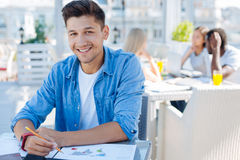 Smart university guy doing homework outdoors. Getting smarter every day. Waist up shot of a relaxed young men enjoying his homework routine while sitting at one Royalty Free Stock Images