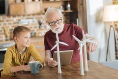 Smart a vieilli l'homme se dirigeant aux modèles de moulin à vent Photographie stock libre de droits