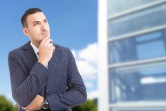 Smart visionary businessman looking up on glass building background. Smart visionary businessman looking up on glass building background as successful stock images