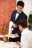 Smart waiter in restaurant Royalty Free Stock Image