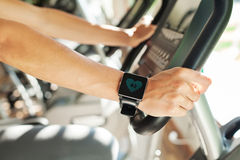 Smart watch on female hand with heart beat on screen. Smart watch showing a heart rate of excercising woman in gym royalty free stock photos