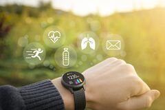 Smart watch, fitness tracker on hand in the outdoor on a blurred green background with icons of basic functions.Concept of The