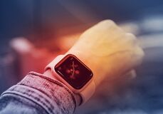 Smart watch on a girl`s hand on a lit red background, the concept of health and modern technology