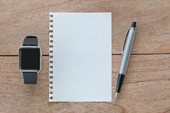 Smart watch with leather bands, blank white paper and silver pen Stock Photos