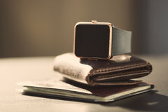 Smart watch, money, documents on the table Royalty Free Stock Images
