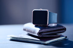 Smart watch, money, documents on the table Stock Images
