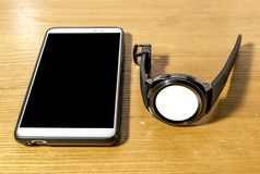 Smart watch and smartphone are on the table stock photos