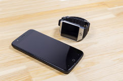 Smart watch and smartphone on wooden background. Stock Image