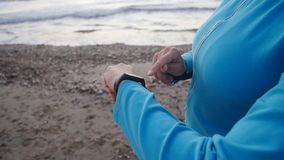 Smart watch woman using smartwatch touching button outdoors. On the beach stock video footage