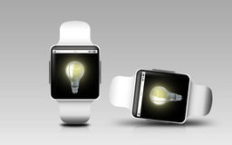 Smart watches with light bulb on screen Royalty Free Stock Photos