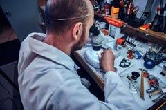 Serious watchmaker  is repairing cutomer`s order at his own repairing studio stock image