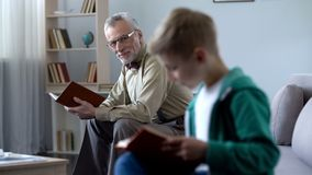 Smart weinig het document van de jongenslezing boek, grootvader het letten op met trots bij hem stock foto