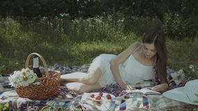 Smart woman applying bookmarks in book outdoors. Gorgeous intelligent woman in summer dress applying bookmarks in hardcover book while lying on blanket in park stock video footage