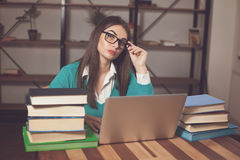 Smart woman with books. Woman is tired. She is working with lots of books and laptop Stock Photos