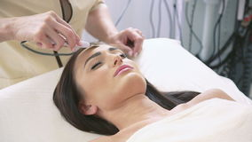 Smart woman getting ultrasonic face procedure in beauty parlor stock footage