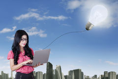 Smart woman with laptop and light bulb Stock Photography