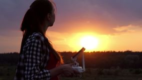Smart woman operates a panel to control a drone at sunset. An impressive view of a young woman who operates a panel with a screen to control a flying drone at a stock video footage