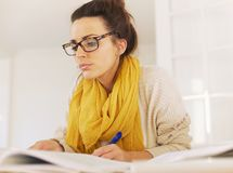 Smart Woman Reading While Taking Notes Royalty Free Stock Photography