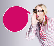 Woman making public speaking announcement. Smart woman sending out a communication message while talking into a large empty speech bubble in a depiction of Stock Photography