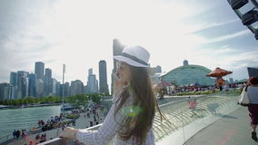 Smart woman stands on embankment and happily chats on cell phone stock video