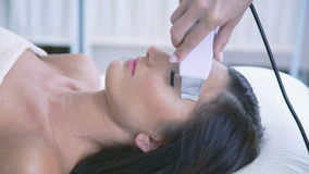 Smart woman on the ultrasonic face procedure at beauty spa stock footage