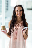 Smart woman using smartphone holding disposable cup Royalty Free Stock Photography