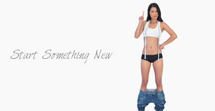 Smart woman wearing jeans falling down because shes lost weight Royalty Free Stock Image