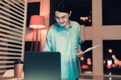 Smart worker watching something at her laptop. Interesting job. Smiling nice worker watching something at her laptop making research royalty free stock image