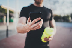 Smart workout session concept.Young Muscular athlete checking training programm on smartphone application after perfect. Workout session at sunny morning Stock Photo