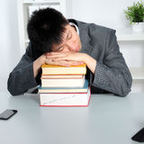 Asian man sleeping on top of a pile of books. Smart young Asian business man or student sleeping on top of a pile of hardcover books while seated at a table in Royalty Free Stock Photography