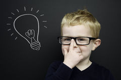 Smart young boy stood infront of a blackboard Stock Photography