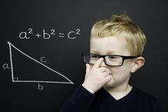 Smart young boy stood infront of a blackboard Stock Photos