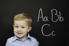 Smart young boy stood infront of a blackboard Royalty Free Stock Photography