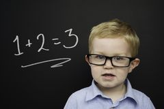 Smart young boy stood infront of a blackboard Royalty Free Stock Photo