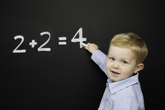 Smart young boy stood writing on a blackboard Stock Photography