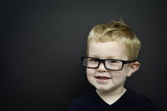 Smart young boy wearing glasses infront of a blackboard Stock Images