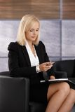 Smart young businesswoman checking phone. Smart young businesswoman checking mobile phone, holding personal calendar, sitting in office armchair Royalty Free Stock Photography