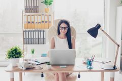 Smart young female professor is working in her office, it is very modern and bright. She is wearing white outfit and glasses stock photography