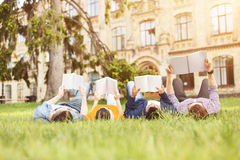 Smart young friends are studying in campus. Pretty four students are preparing for lessons together. They are lying on grass near a university. Man and women are Stock Images